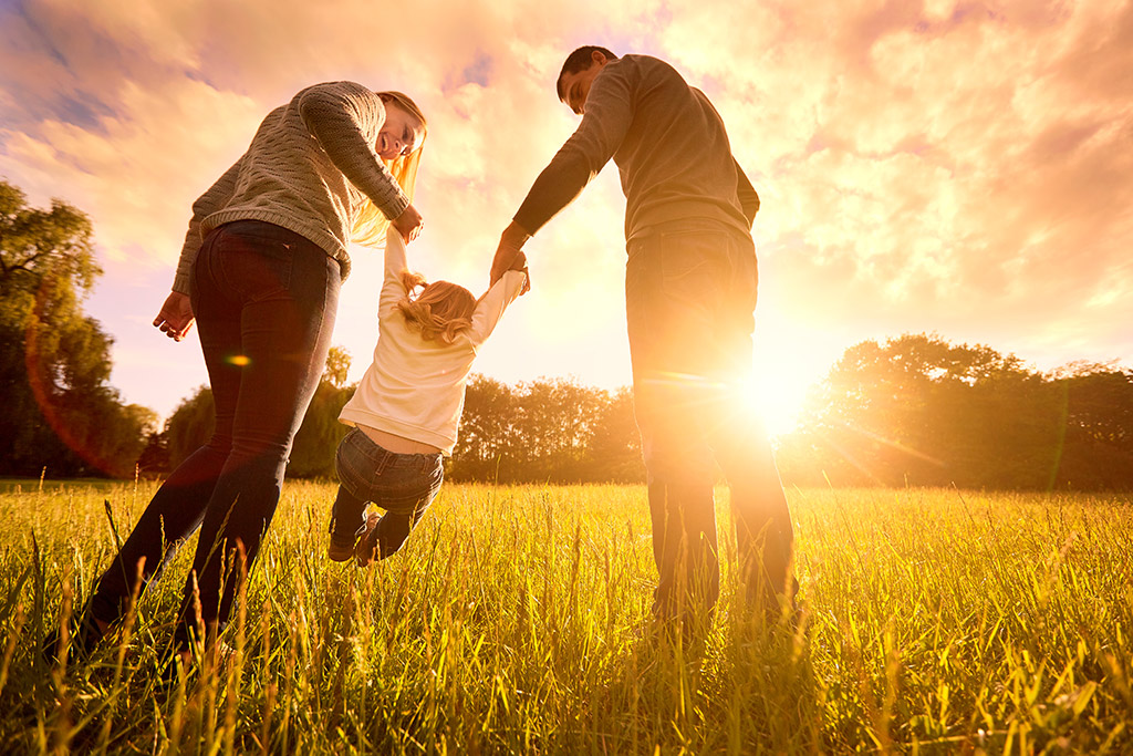 family running in a field and happy with their insurance choices